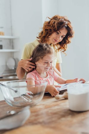 Photo for Selective focus of mother touching hair of daughter while reading cookbook together at kitchen table - Royalty Free Image