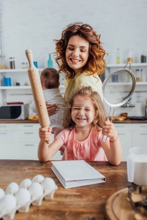 Photo for Selective focus of girl holding rolling pin and sieve near mother with infant son - Royalty Free Image