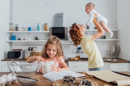 selective focus of girl touching flour in measuring jug near mother holding infant son above head