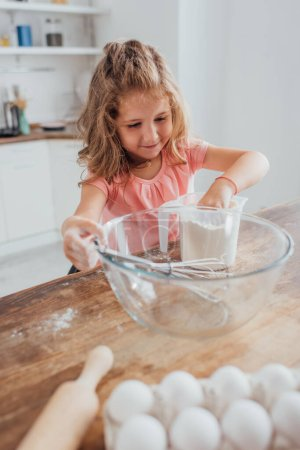 selective focus of child mixing flour in measuring jug near glass bowl, rolling pin and chicken eggs