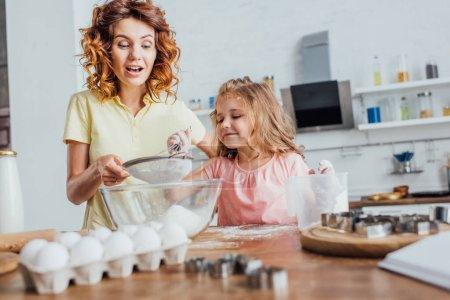 selective focus of curly woman sieving flour into glass bowl near daughter, chicken eggs and cookie cutters