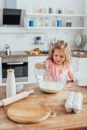 selective focus of child mixing flour in glass bowl with whisk near bottle of milk, rolling pin and eggs on kitchen table