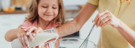 cropped view of mother holding whisk and pouring milk into glass bowl together with daughter, panoramic shot