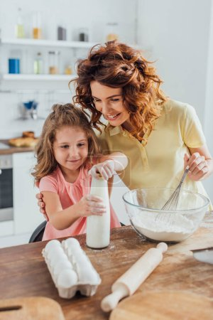Photo for Woman holding whisk near bowl with flower and touching daughter opening bottle of milk - Royalty Free Image