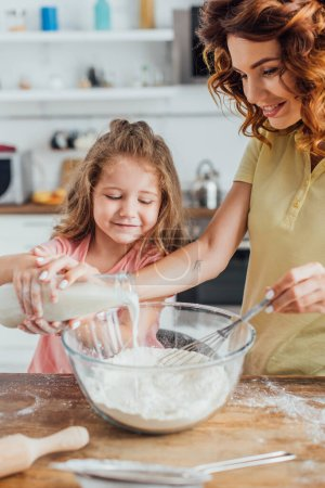 selective focus of girl with mother pouring milk into glass bowl with flour