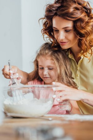 selective focus of young mother kneading dough in glass bowl near daughter