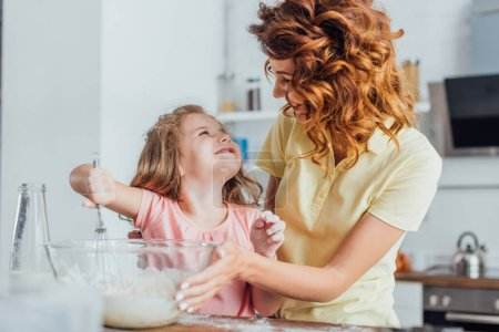 Photo for Selective focus of girl kneading dough in glass bowl while looking at curly mother - Royalty Free Image