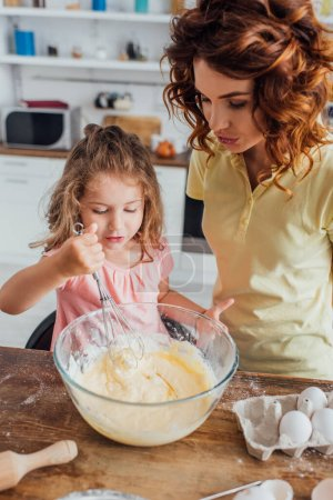 Photo for High angle view of girl kneading dough with whisk in glass bowl near mother - Royalty Free Image