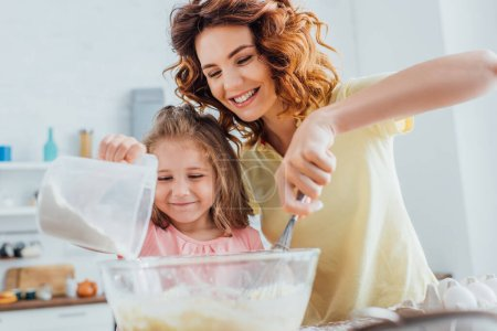 selective focus of mom kneading dough in glass bowl near daughter