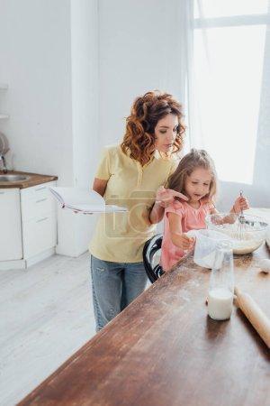 enfoque selectivo de la madre sosteniendo libro de cocina y señalando con el dedo cerca de la hija amasando masa en un tazón de vidrio