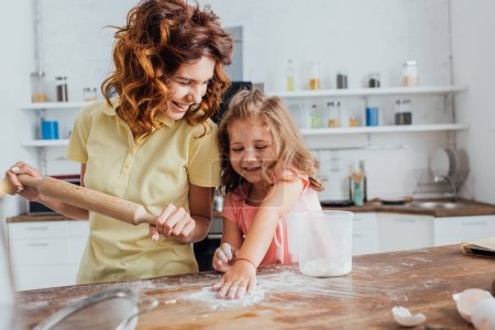 Photo for Selective focus of mother holding rolling pin near daughter scattering flour on kitchen table - Royalty Free Image
