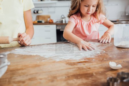 cropped view of mother standing near daughter scattering flour on kitchen table