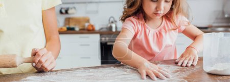 cropped view of mother standing near daughter scattering flour on wooden table in kitchen