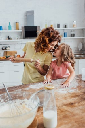 Photo for Selective focus of mother holding rolling pin and daughter scattering flour while standing face to face at kitchen table - Royalty Free Image
