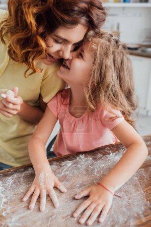 Photo pour Vue grand angle de fille parlant à la mère tout en dispersant la table de cuisine avec de la farine - image libre de droit