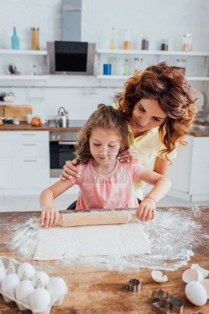 Photo for Selective focus of woman touching shoulders of daughter rolling out dough near chicken eggs and cookie cutters - Royalty Free Image