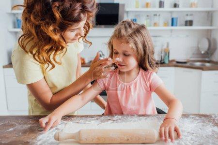 Mutter berührt Nase der Tochter beim Ausrollen von Teig auf mit Mehl bestreutem Tisch