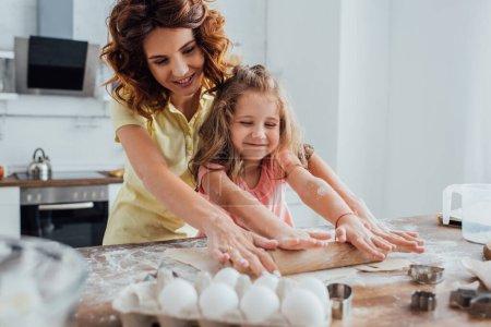 Photo pour Foyer sélectif de mère et fille déroulant la pâte près des oeufs de poulet et des emporte-pièces sur la table - image libre de droit