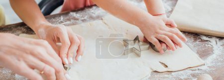 partial view of woman and child cutting out cookies from rolled dough near star-shaped mold, panoramic concept