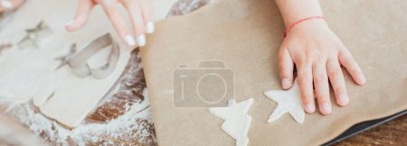 partial view of child putting raw multi-shaped cookies on baking paper near mother and rolled dough, panoramic shot