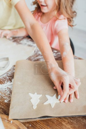 partial view of woman with daughter putting raw multi-shaped cookies on baking paper, selective focus