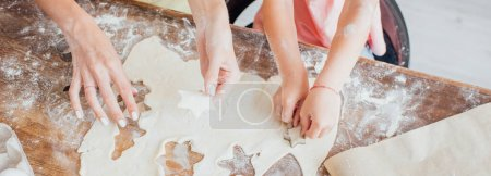 cropped view of mom and kid cutting out multi-shaped cookies from rolled dough