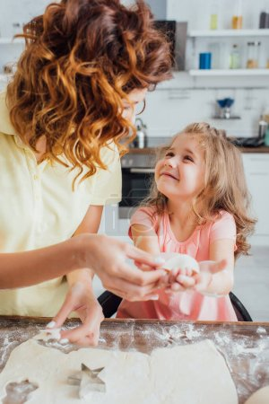 selective focus of mother holding raw cookie near daughter, rolled dough and star-shaped mold