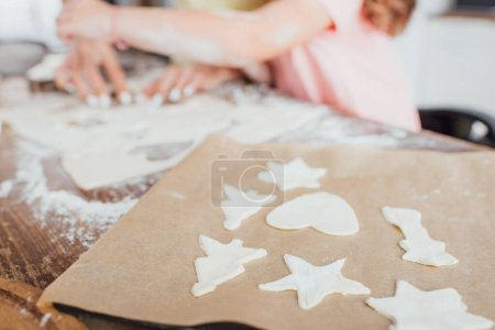cropped view of mother and daughter near baking paper with raw multi-shaped cookies on kitchen table, selective focus