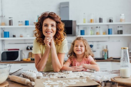 young mother and daughter looking at camera near raw cookies and ingredients on kitchen table