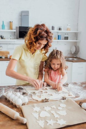 selective focus of curly mother and blonde daughter cutting out cookies from rolled dough