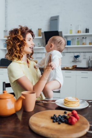 young, curly mother holding infant son near table served with pancakes and fresh berries
