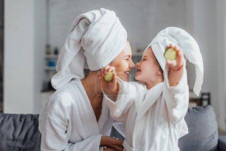 Photo pour Jeune femme avec fille en peignoirs blancs et serviettes sur les têtes assises face à face tandis que la fille tenant des tranches de concombre frais - image libre de droit