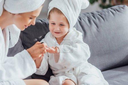 enfoque selectivo de la madre joven haciendo manicura a la hija en albornoz blanco y toalla en la cabeza