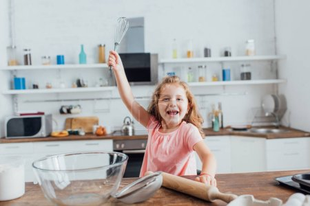 kid holding whisk in raised hand near rolling pin, glass bowl and sieve on kitchen table