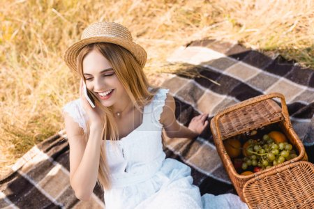 high angle view of blonde woman in white dress and straw hat talking on smartphone near wicker basket with fruits