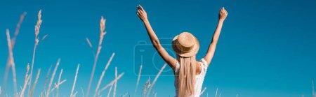 Photo pour Vue arrière de la femme en chapeau de paille debout avec les mains levées contre le ciel bleu, culture panoramique - image libre de droit