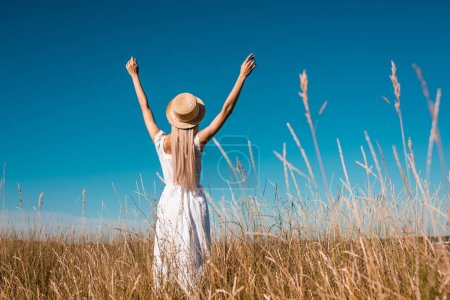 back view of stylish woman in white dress and straw hat standing in grassy meadow with raised hands against blue sky