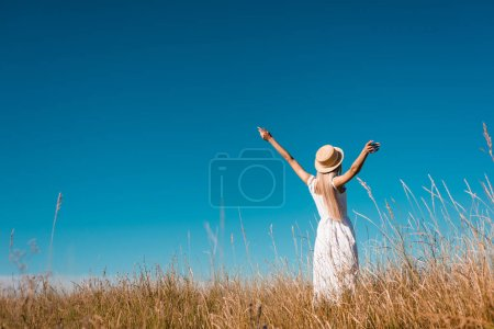 back view of woman in white dress and straw hat standing with outstretched hands in grassy field against blue sky