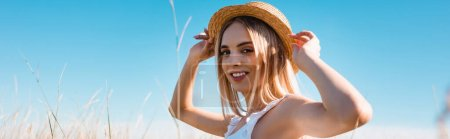 selective focus of young blonde woman touching straw hat and looking at camera against blue sky, panoramic concept