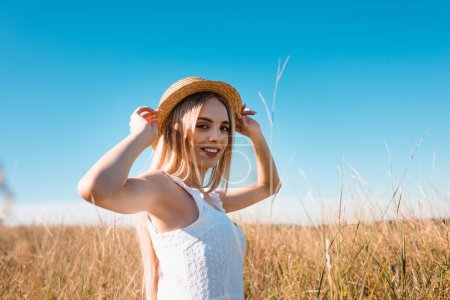 selective focus of sensual blonde woman touching straw hat and looking at camera in grassy field