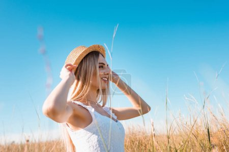 Photo for Selective focus of stylish blonde woman touching straw hat while looking away against blue sky - Royalty Free Image