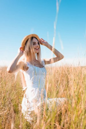 selective focus of stylish blonde woman in white dress looking away and touching straw hat while sitting in grassy meadow