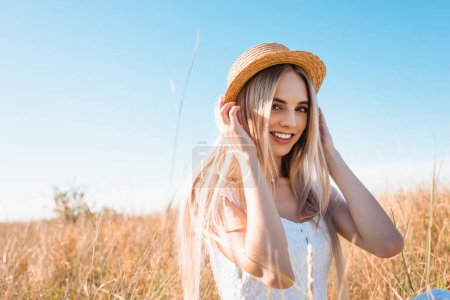 selective focus of blonde woman looking at camera and touching straw hat while sitting in sunshine against blue sky