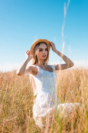 selective focus of young blonde woman in white dress sitting in field and touching straw hat while looking at camera