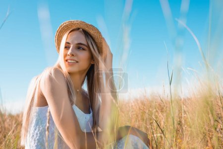 selective focus of stylish blonde woman looking away while sitting in field and touching straw hat