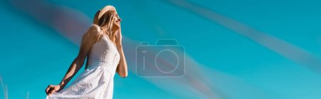 selective focus of young woman touching white dress against blue sky, panoramic concept