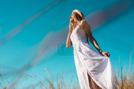 low angle view of sensual woman touching white dress while standing against blue sky