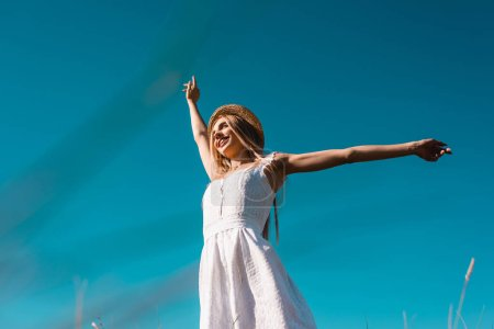 Photo for Low angle view of woman in white dress and straw hat looking away while standing against blue sky with outstretched hands - Royalty Free Image