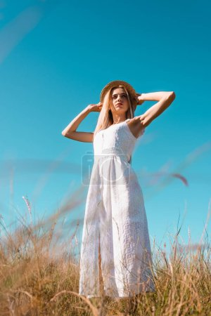 selective focus of young woman in white dress touching straw hat while looking away against blue sky, low angle view