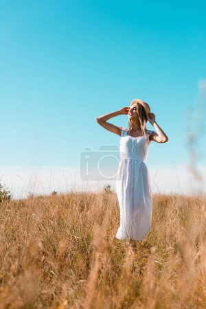 selective focus of blonde woman in white dress touching straw hat while standing in meadow against blue sky